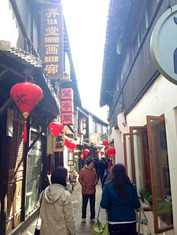people standing in alleyway with red lanterns and open windows