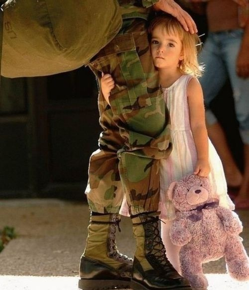 little girl clutching teddy bear and adult's leg