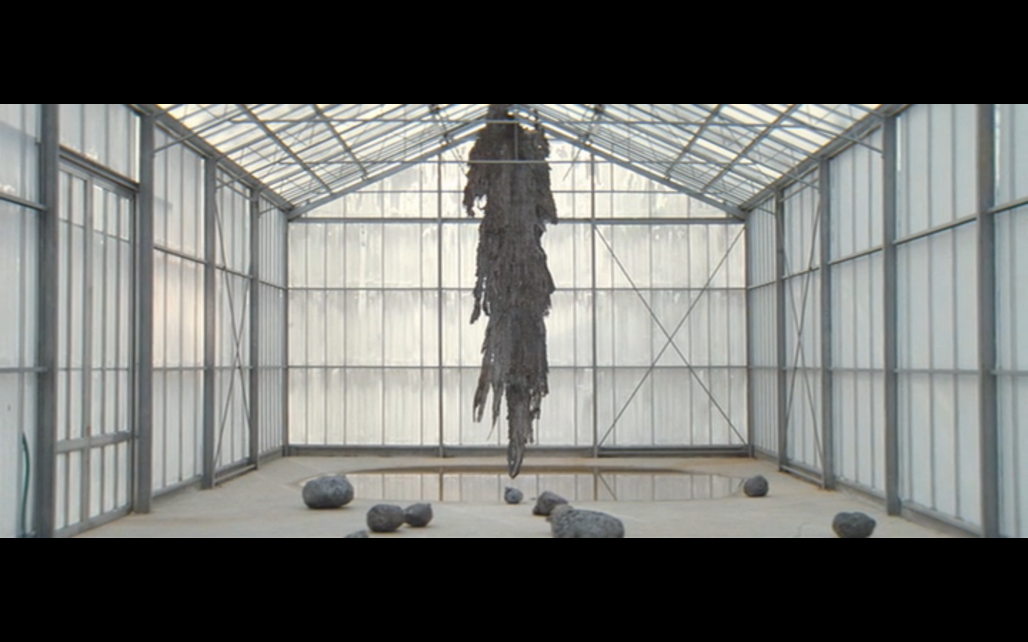 room with sculture hanging from ceiling and rocks on ground
