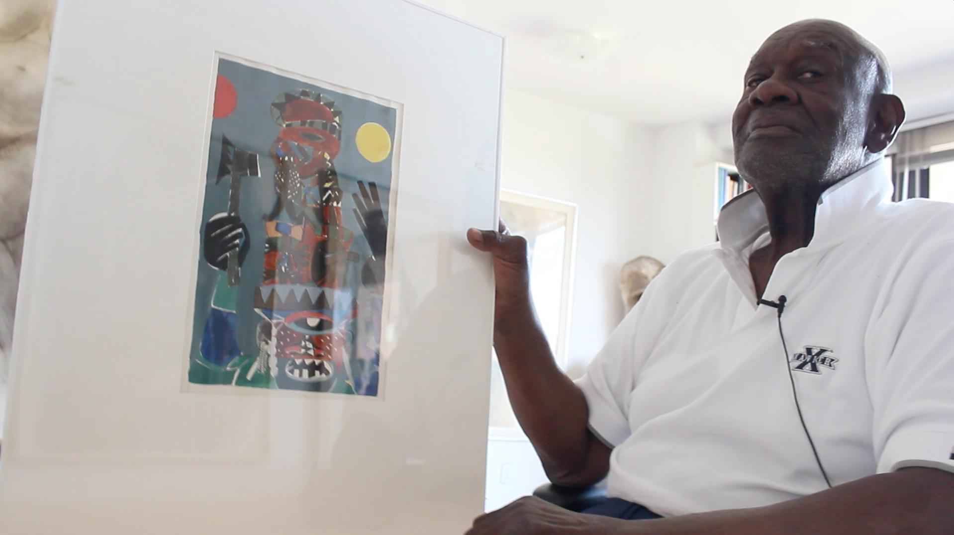 (still grab) man holding artwork