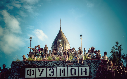 crowd of people sitting on sign at Фузион (fusion) music festival