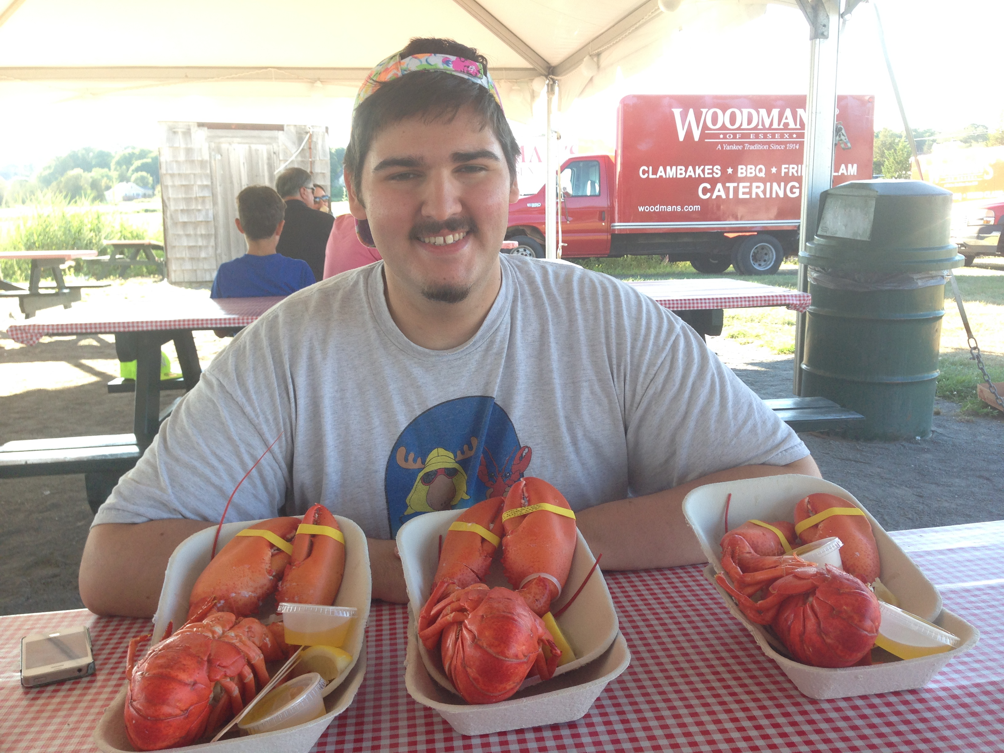 man sitting at picnic table with three lobsters