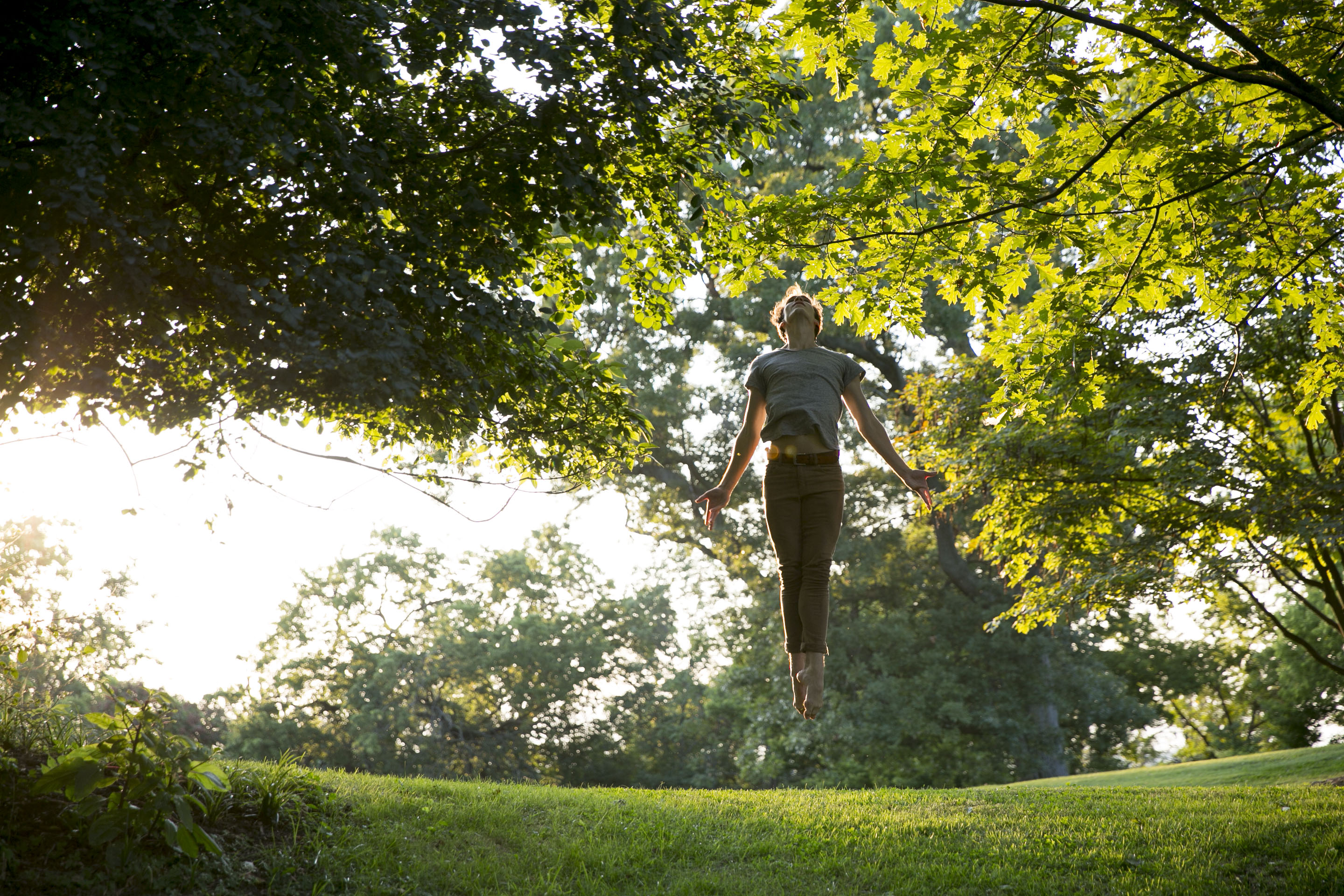 person jumping and dancing under trees