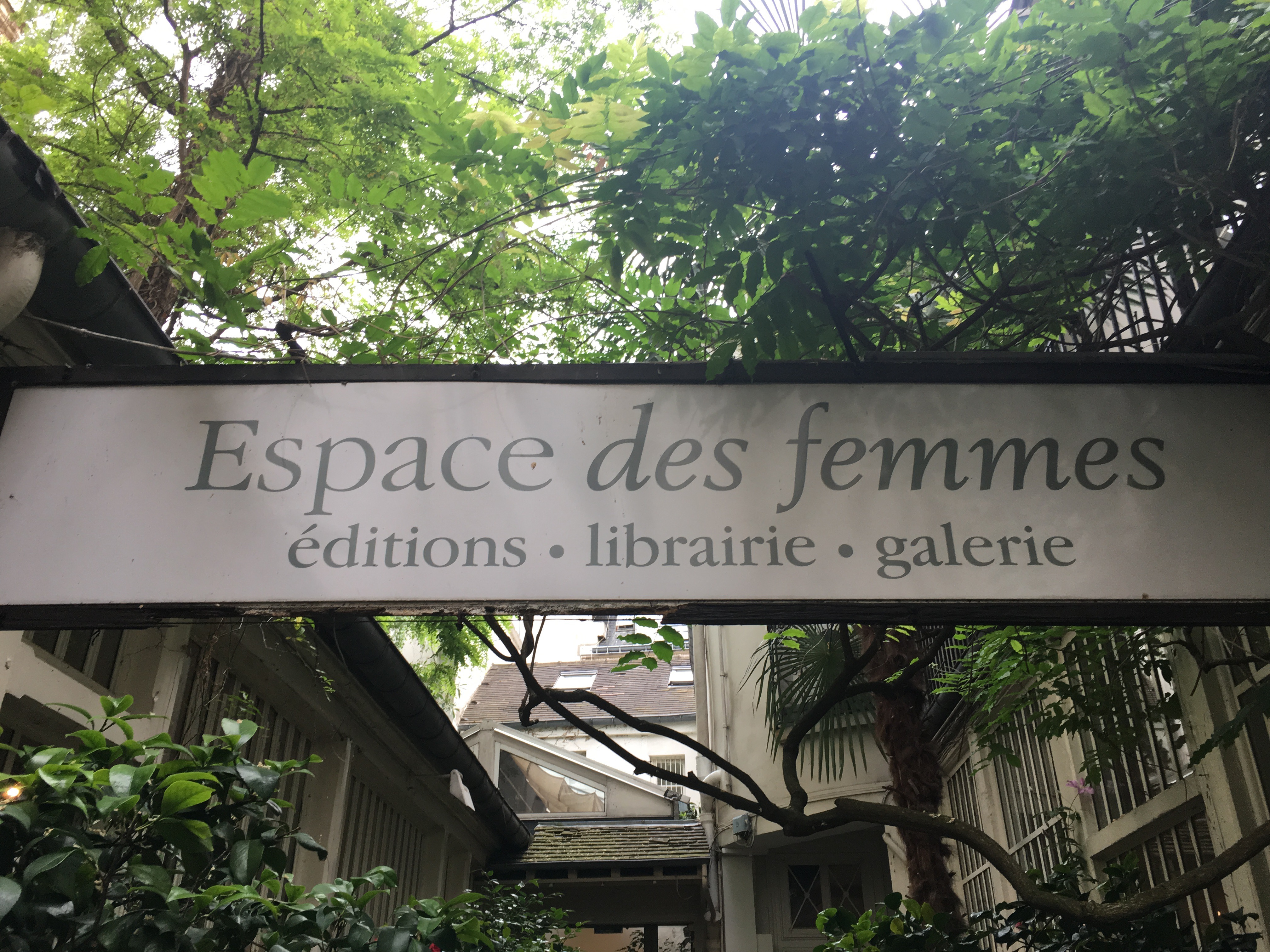 """sign that says """"Espace des femmes"""" in front of trees"""