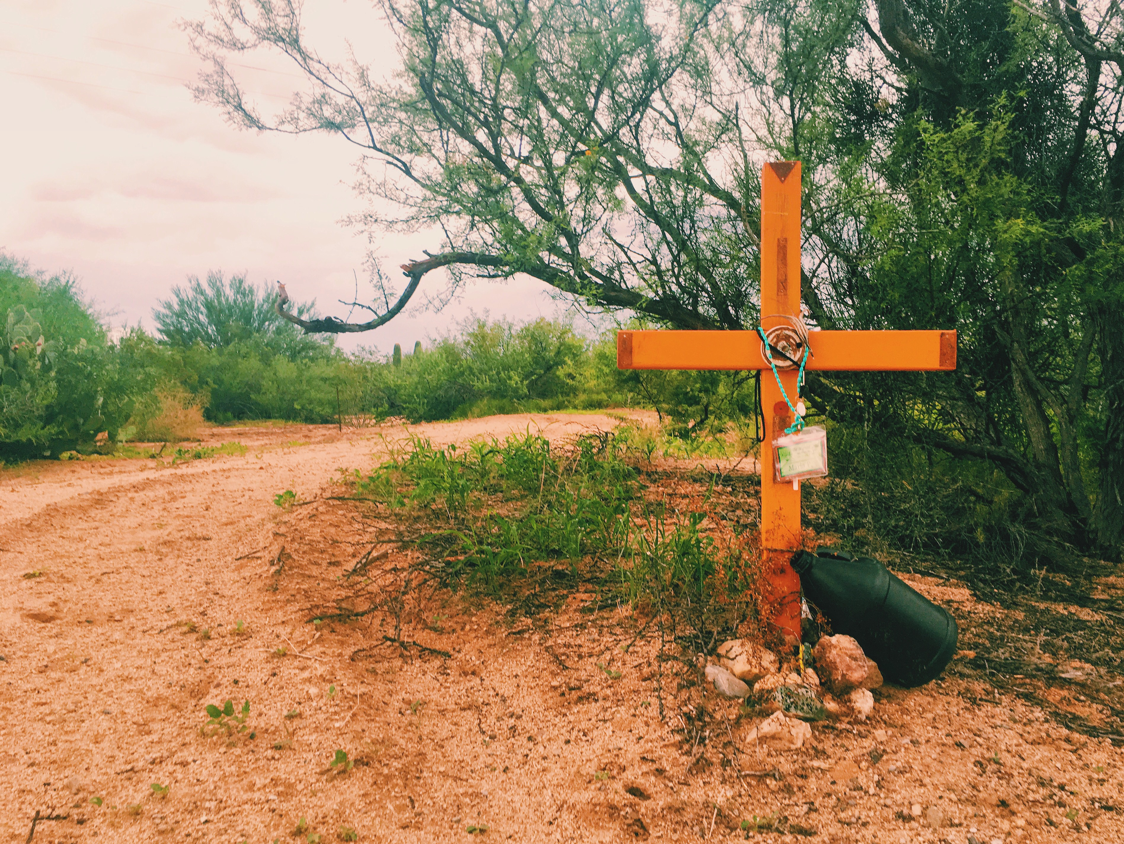 memorial with large cross on dirt road
