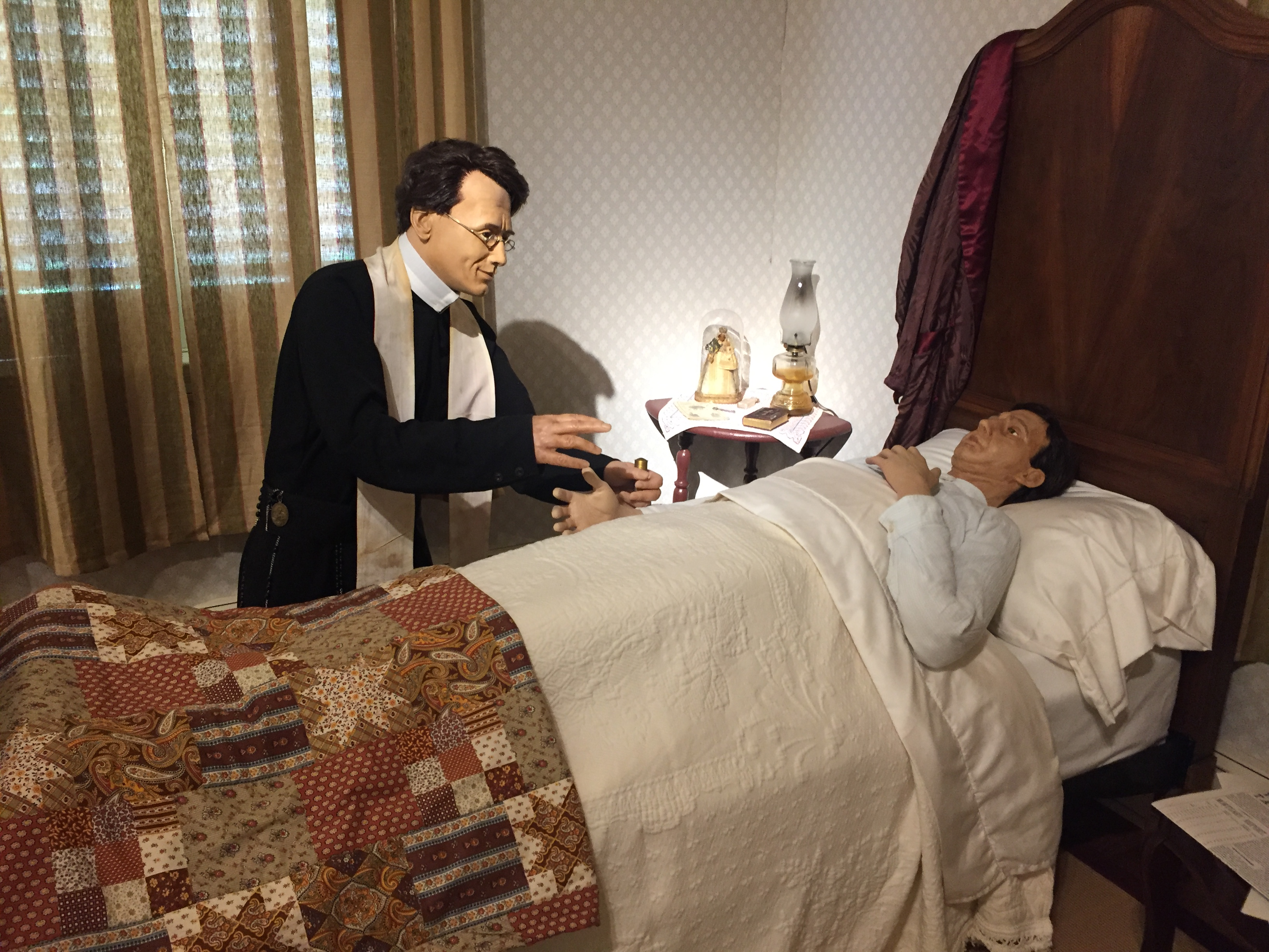 statues of man hovering over sick man in bed
