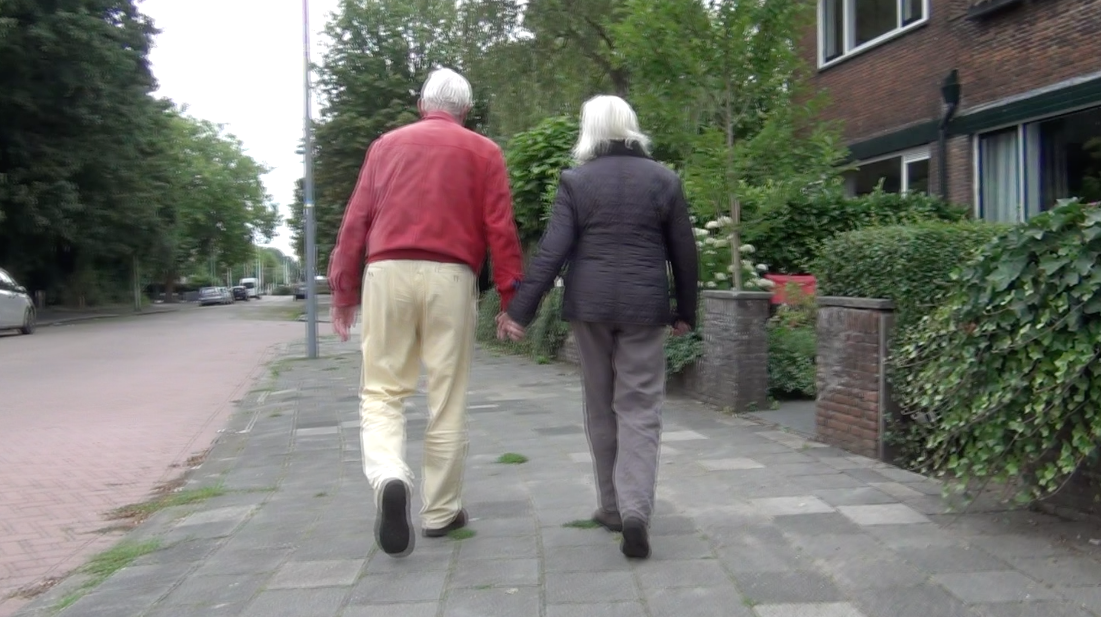 two people walking hand in hand outside