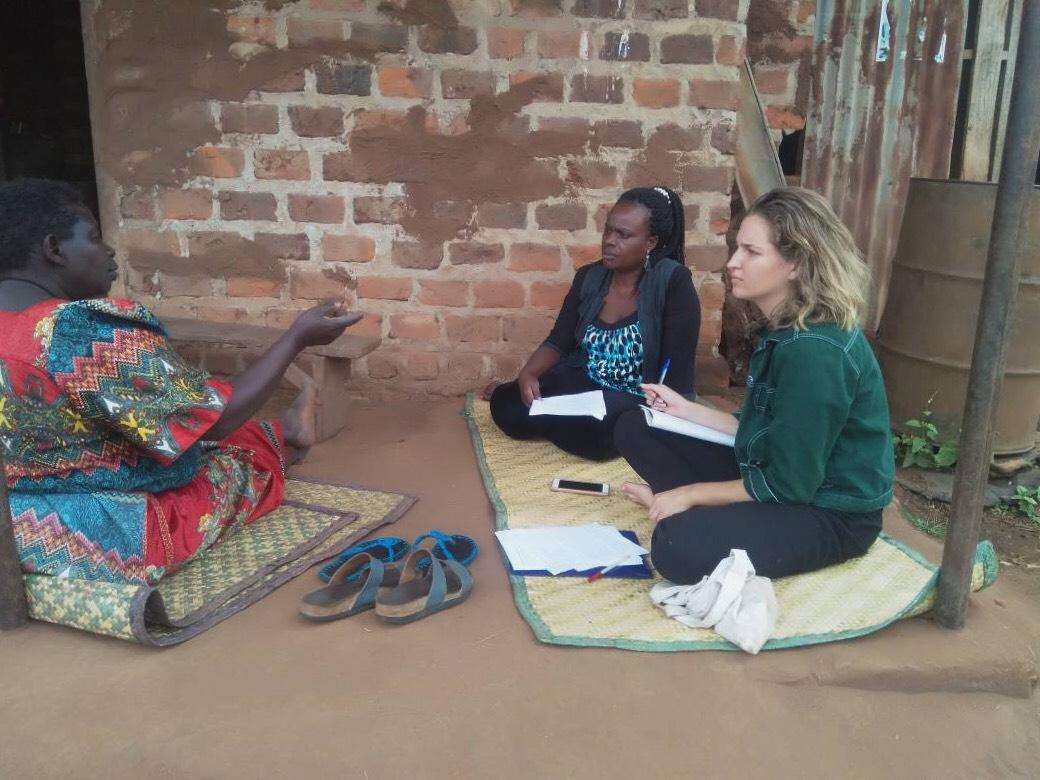 three women in Uganda sitting on mats and talking