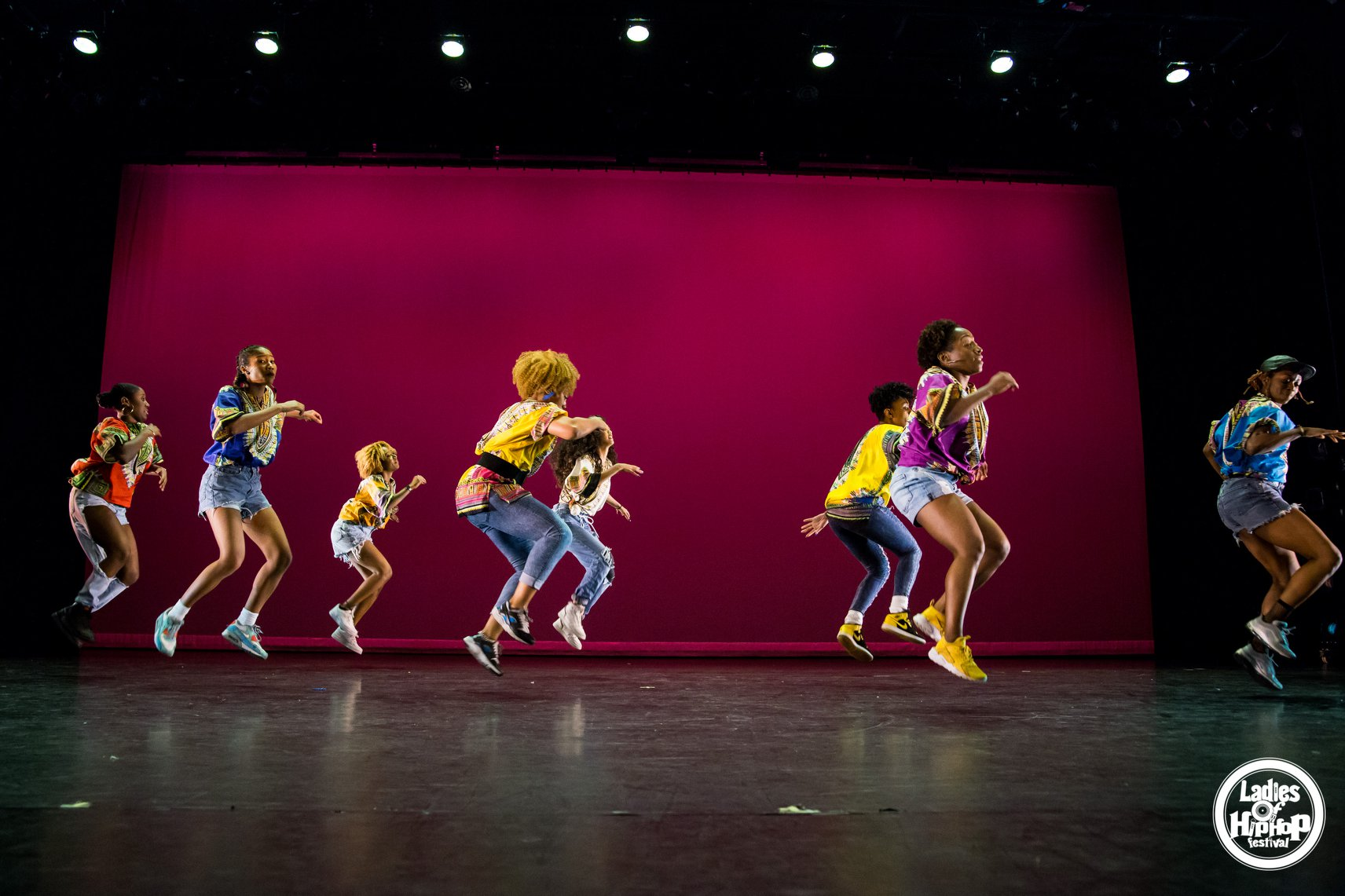 group of people dancing and jumping in air in unison