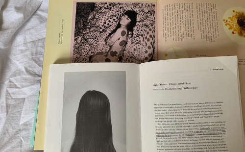 """Two open books - one is """"Feelings,"""" an art book with works and interviews by dozens of contemporary artists/musicians/influencers/etc, and lying on top of it is """"Out There: Marginalization and Contemporary Culture"""" on an essay by Audre Lorde"""